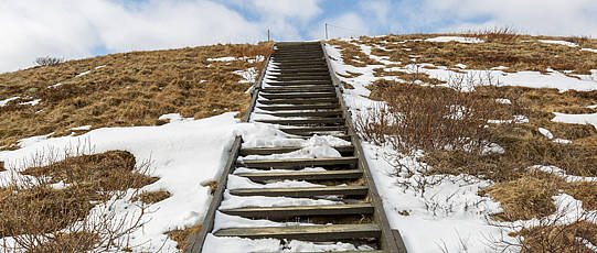 Stairs leading up to a partly snowy hill.