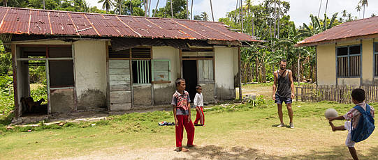 Children play football in front of two huts.