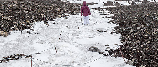 Trail markings with hiker on snowy mountain.