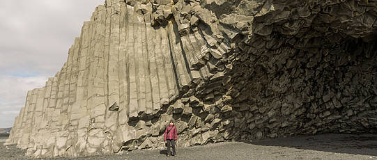 Man in a red jacket in front of columnar rock formations.