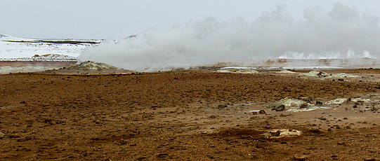 Smoking geyser on brown ground with snowy hills in the background.