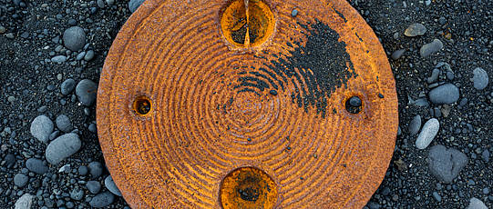 Round, rusty metal piece with decorative grooves on black sand and pebbles.